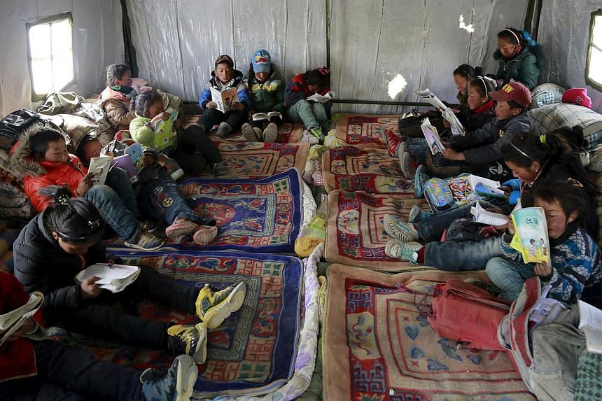 Third-grade students read in a class at a relief tent after the 7.9-magnitude earthquake hit Nepal. The earthquake has left almost a million children without classrooms, the UN children's agency says, calling for urgent action to repair damaged schoo