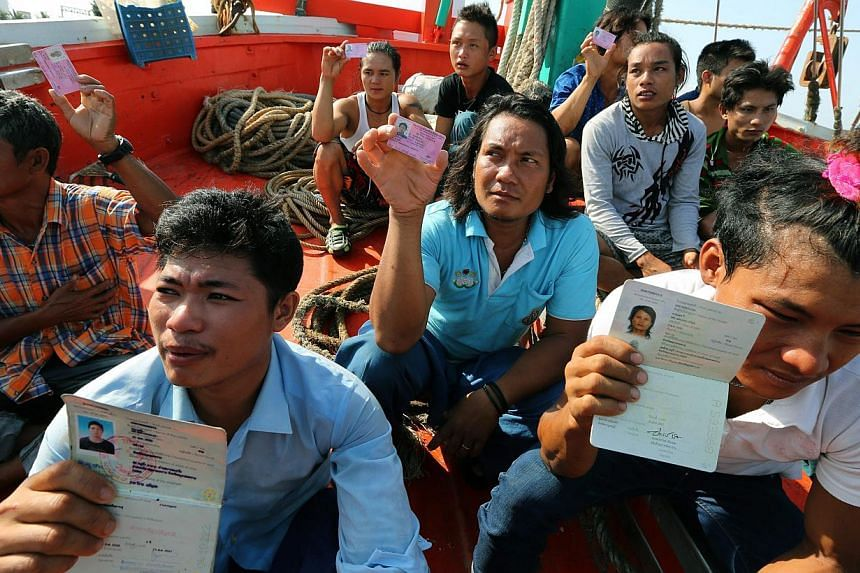 Migrant workers show their migrant worker cards as Thai authorities inspect a fishing boat in Mae Klong district, Samut Songkhram province, Thailand, on May 7, 2015. -- PHOTO: EPA