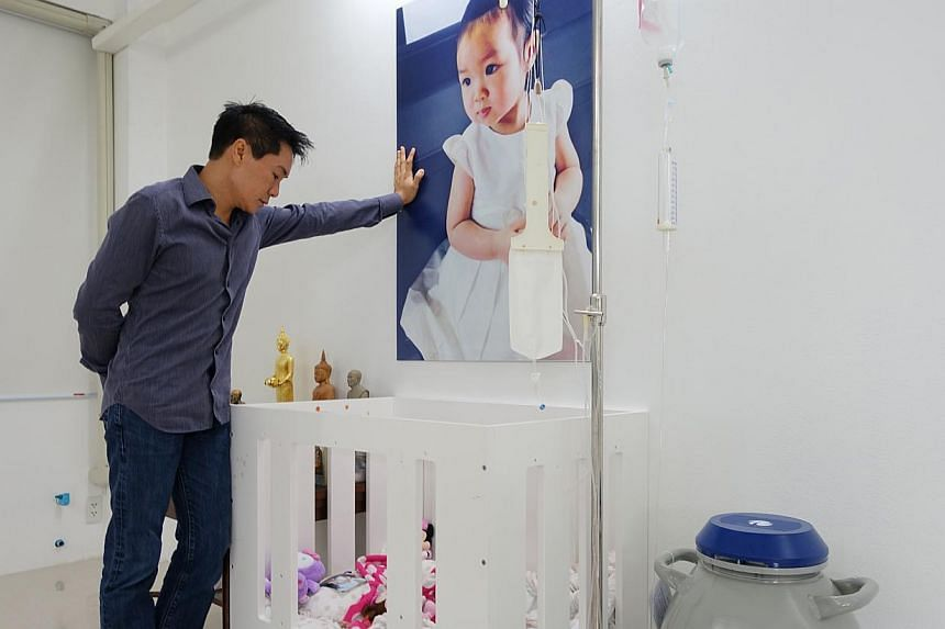 Dr Sahatorn Naovaratpong, a businessman, at the cot where his daughter, Matheryn, used to sleep when she was battling brain cancer, until her death in January 2015. -- ST PHOTO: TAN HUI YEE