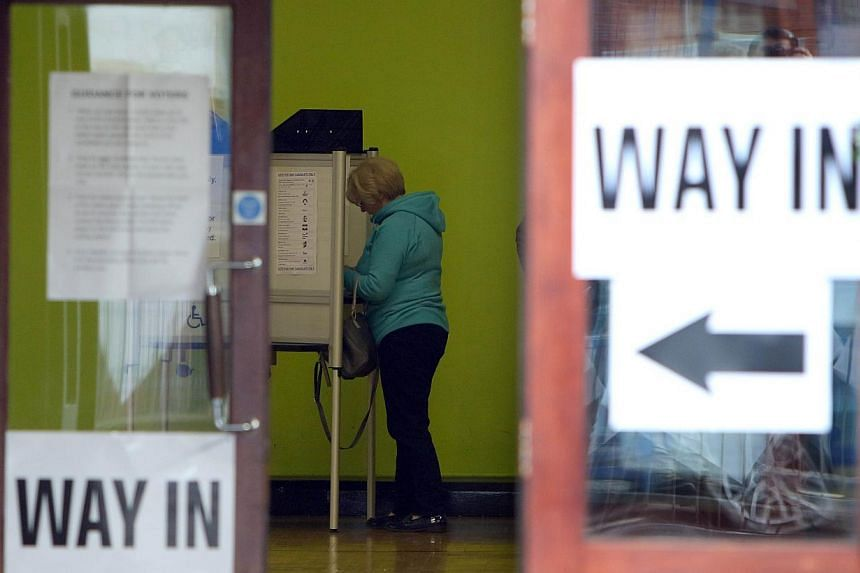 A voter prepares to cast her vote in Belfast on May 7, 2015. -- PHOTO: AFP