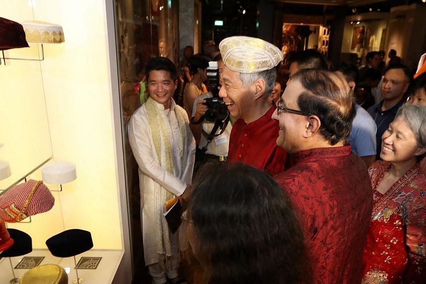 Prime Minister Lee Hsien Loong tries on a traditional Indian headgear as his wife Ho Ching and Minister in the Prime Minister's Office S. Iswaran look on. They were at the opening of the $21 million Indian Heritage Centre in Campbell Lane on May 7,