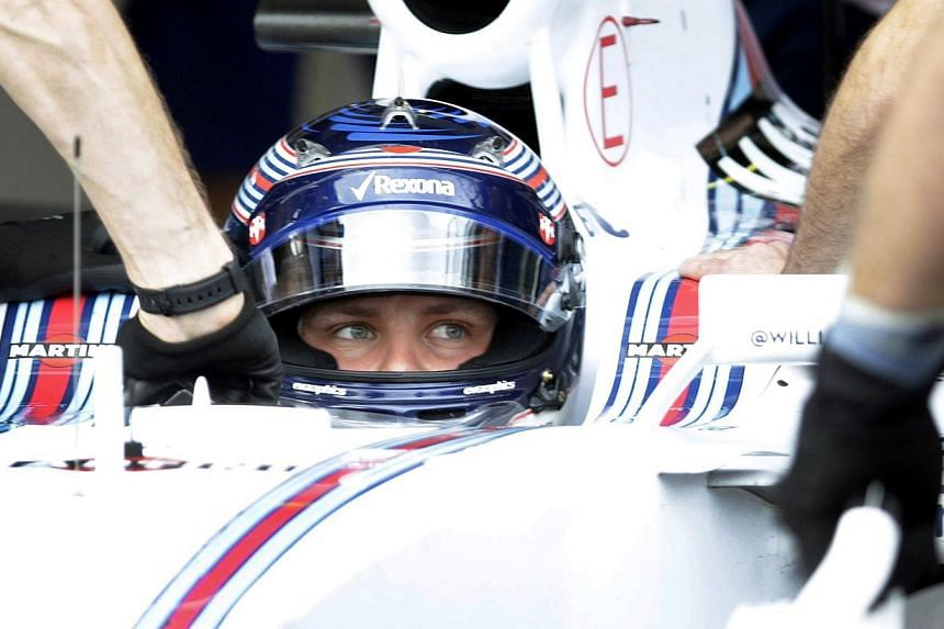Williams Martini Racing's Finnish driver Valtteri Bottas sits in the pits during qualifying for the Formula One Australian Grand Prix in Melbourne on March 14, 2015. -- PHOTO: AFP