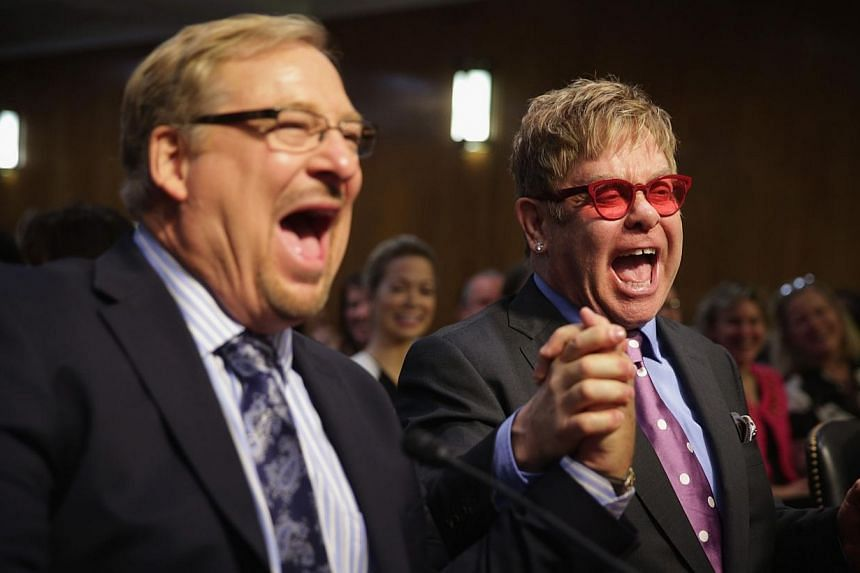 Singer/songwriter Elton John (right) and pastor of the Saddleback Church Rick Warren (left) shake hands prior to a hearing before the State, Foreign Operations and Related Programs Subcommittee of the Senate Appropriations Committee on Tuesday on Cap