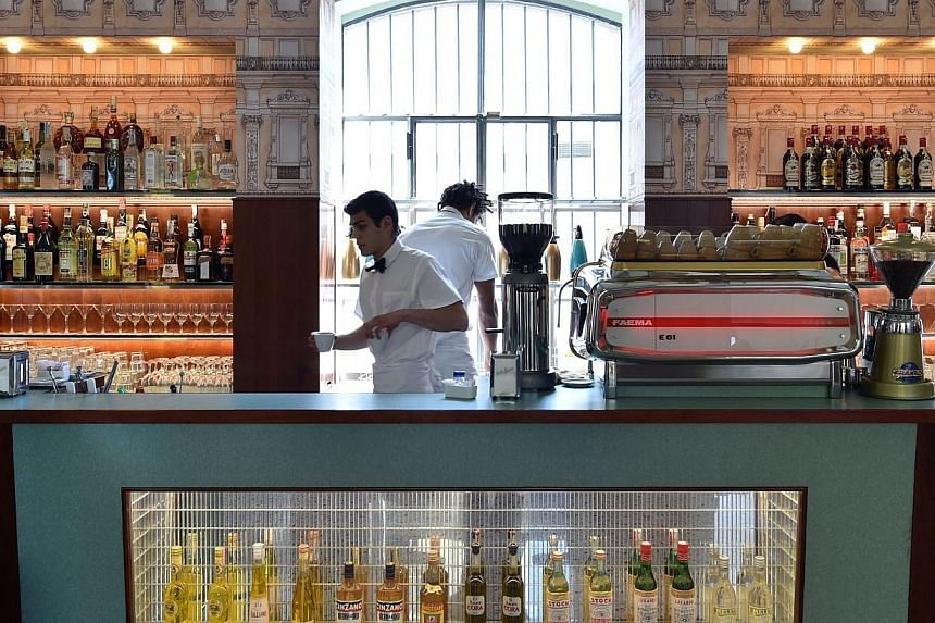Waiters work in a bar designed by US film director Wes Anderson recreating the old Milan cafes' atmosphere in the new venue of Prada's Foundation on Saturday in Milan. -- PHOTO: AFP