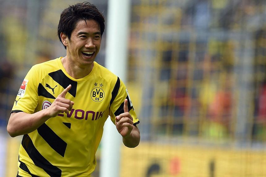Shinji Kagawa (above), Marco Reus and the rest of Borussia Dortmund's star-studded squad will be showcasing their football skills in Asia this July - including a stopover in Singapore. -- PHOTO: AFP