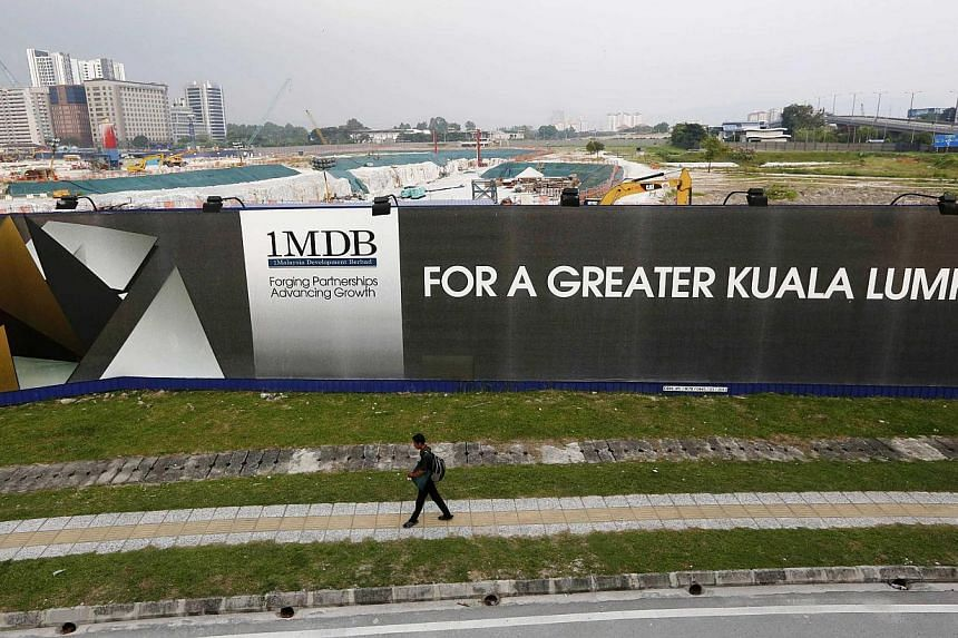 A man walking past a 1MDB billboard at the funds flagship Tun Razak Exchange development in Kuala Lumpur, in this on March 1, 2015 file photo. -- PHOTO: REUTERS