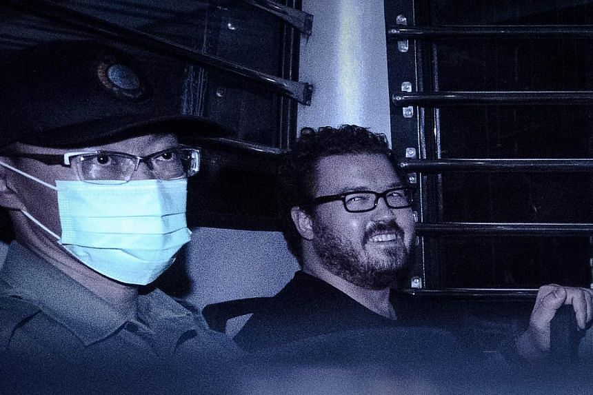 British banker Rurik Jutting (right), charged with the grisly murders of two women, smiles as he sits in a prison van leaving the eastern court in Hong Kong on Nov 10, 2014. -- PHOTO: AFP