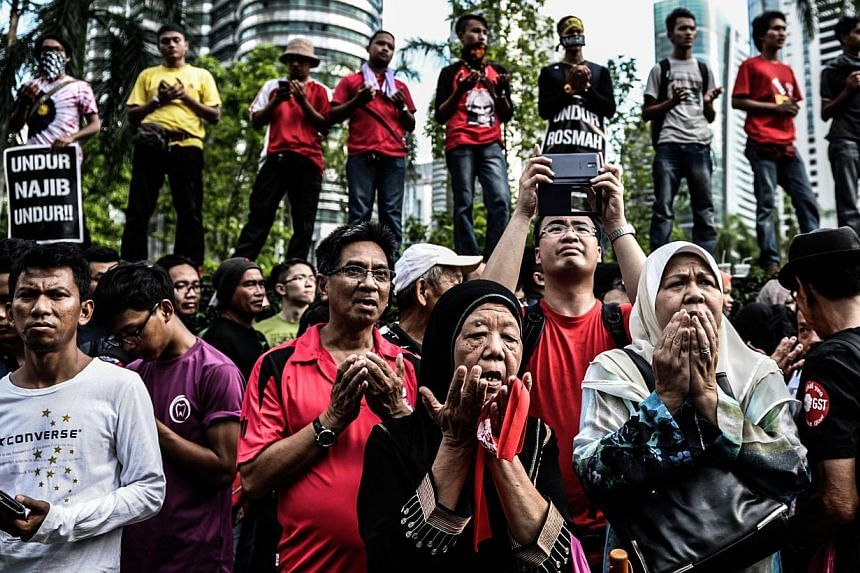 Protesters offering prayers during a May Day rally against the goods and services tax in front of the Petronas Twin Towers in Kuala Lumpur. According to think-tank Khazanah Research Institute, Malaysia's poorest are struggling to cope with surging fo