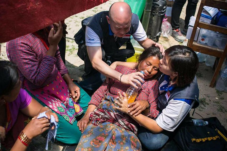 Quake survivors preparing a meal at an open-ground shelter area in Kathmandu on Tuesday. For those forced to camp outside, relief organisations say tarpaulins are more suitable than tents, which can weigh up to 80kg. Mercy Relief Singapore chairman M