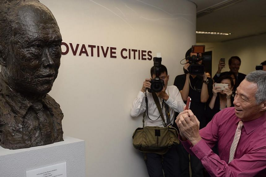 PM Lee Hsien Loong takes a picture of a bust of his father, the late Mr Lee Kuan Yew, at theSingapore University of Technology and Designduring its official opening on May 8, 2015. -- ST PHOTO: MARK CHEONG