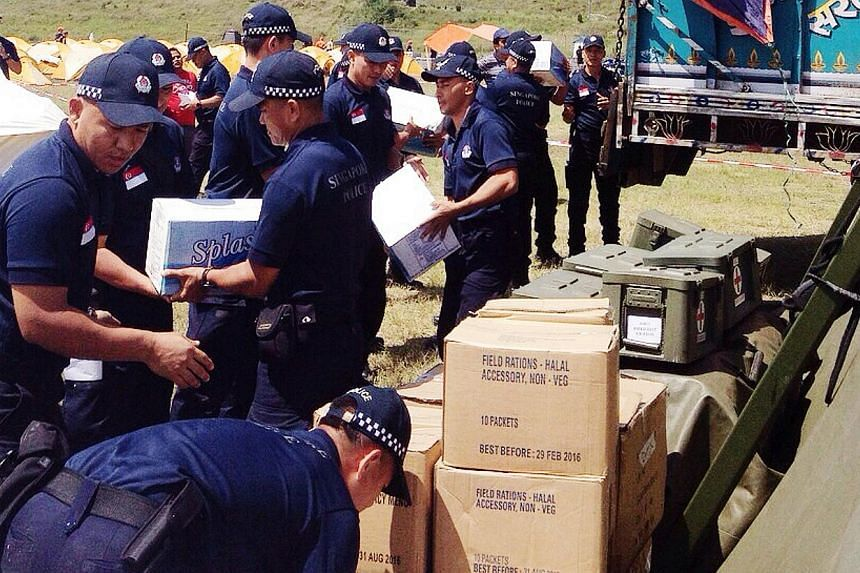 Singapore police officers from the Home Team contingent loading supplies bound for Pokhara base from where it is coordinating the humanitarian operations in Gorkha district. -- PHOTO: MHA
