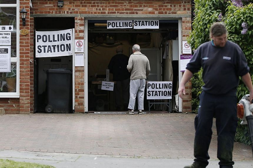 A man arrives to vote at a polling station set up in the garage of a house in Croydon on Tuesday, as Britain holds a general election. -- PHOTO: AFP