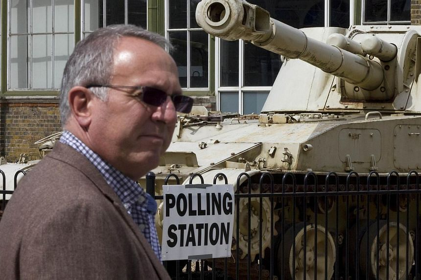 A man passes a 2S3 M-1973 Akatsiya 152-mm self-propelled gun howitzer tank outside the Greenwich Heritage Centre, set up as a polling station in London on Thursday, as Britain holds a general election. -- PHOTO: AFP
