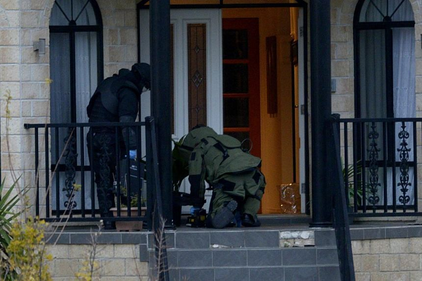 Officers wearing bomb suits raiding a home in Greenvale, Melbourne, on May 8, 2015. -- PHOTO: EPA