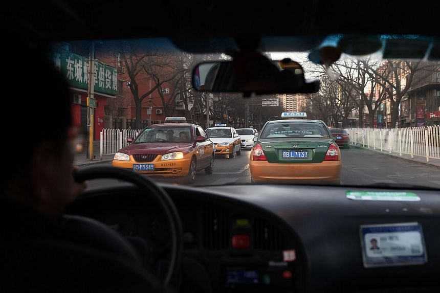 A Feb 16, 2015 photo shows a taxi driver following another taxi on a street in Beijing. China's crackdown on ride-sharing app Uber may have less to do with protecting the owners of politically powerful taxi services than placating the taxi industry's
