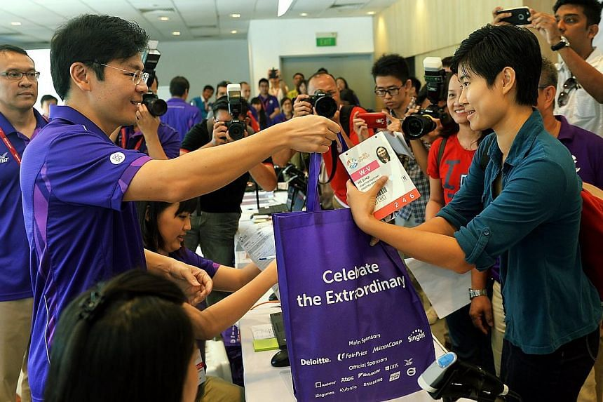 Volunteer Miss Yee Si Hui 21, received the Sea Games bag from Culture, Community and Youth Minister Lawrence Wong. -- PHOTO: BERITA HARIAN