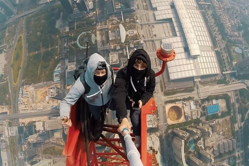 Daredevil climbers Vadim Makhorov and Vitaly Raskalov taking a selfie on top of the crane on the roof of the 660m Ping An International Financial Centre in Shenzhen, China. -- PHOTO: ON THE ROOFS/YOUTUBE