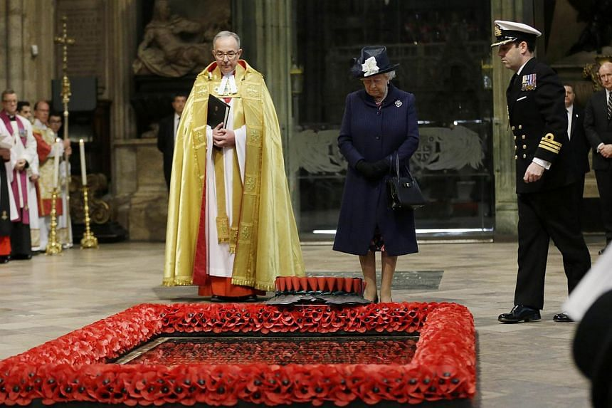 Britain's Queen Elizabeth II (centre right) looks down after a wreath was laid on her behalf at the grave of the Unknown Warrior flanked by the Dean of Westminster John Hall (centre left) at the start of a service of national thanksgiving to mark the