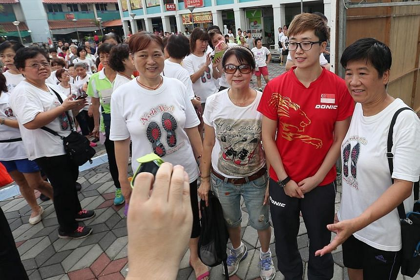 Team Singapore athlete, paddler Feng Tian Wei (in red), joins residents in a monthly community sporting event - Active Day - at Khatib Plaza on May 10, 2015. -- ST PHOTO: NEO XIAOBIN