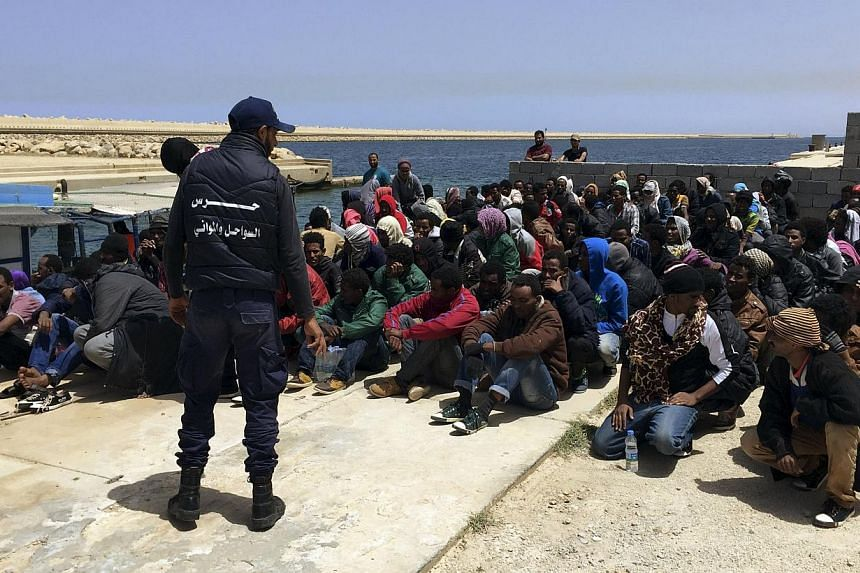 A coast guard (back to camera) stands over illegal migrants who attempted to sail to Europe, on the shore after the migrants' boat was intercepted at sea by the Libyan coast guard, at Khoms, Libya onMay 6, 2015. Defence ministers from five Euro