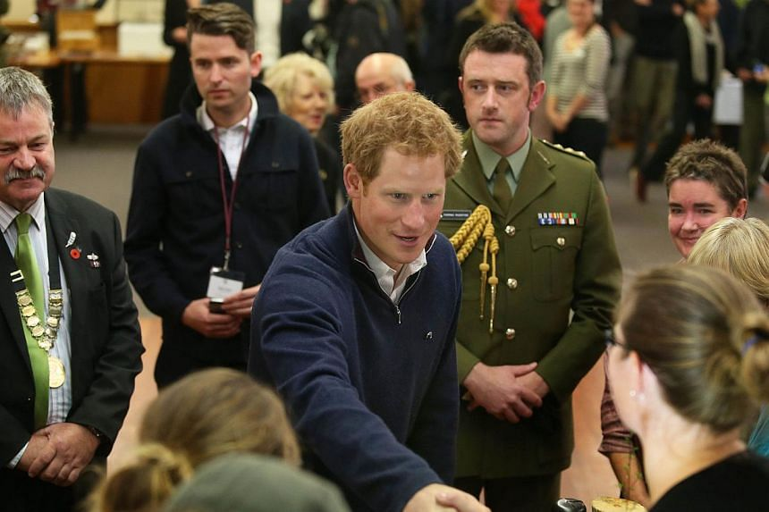 Britain's Prince Harry (centre) shakes hands with locals during a visit to the Stewart Island Community Centre in Oban, Stewart Island, as part of his first visit to New Zealand on May 10, 2015. -- PHOTO: AFP