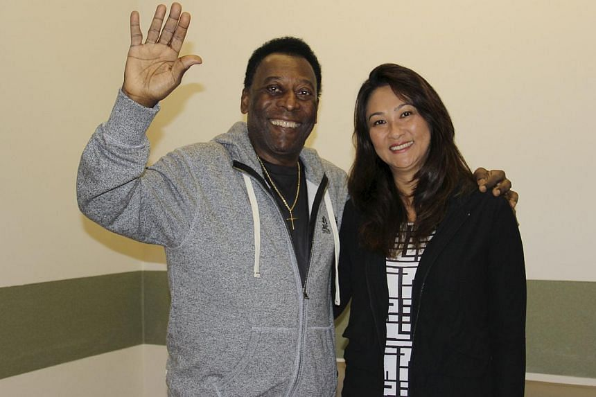 Pele (left) waves with his wife Marcia Cibele Aoki at the Albert Einstein Hospital in Sao Paulo in this May 9, 2015 handout photograph from his family, courtesy of the hospital. The Brazilian soccer legend left hospital on Saturday after undergoing p