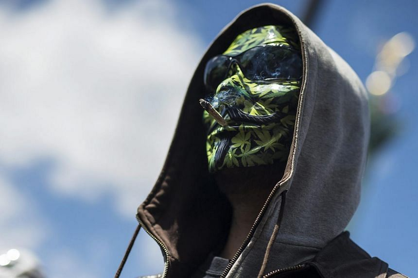 A protestor, wearing an anonymous mask with hemp leaves painted on it, smokes cannabis during a demonstration for the legalisation and re-classification of the substance at Place de la Bastille in Paris, France, on May 9, 2015. -- PHOTO: EPA