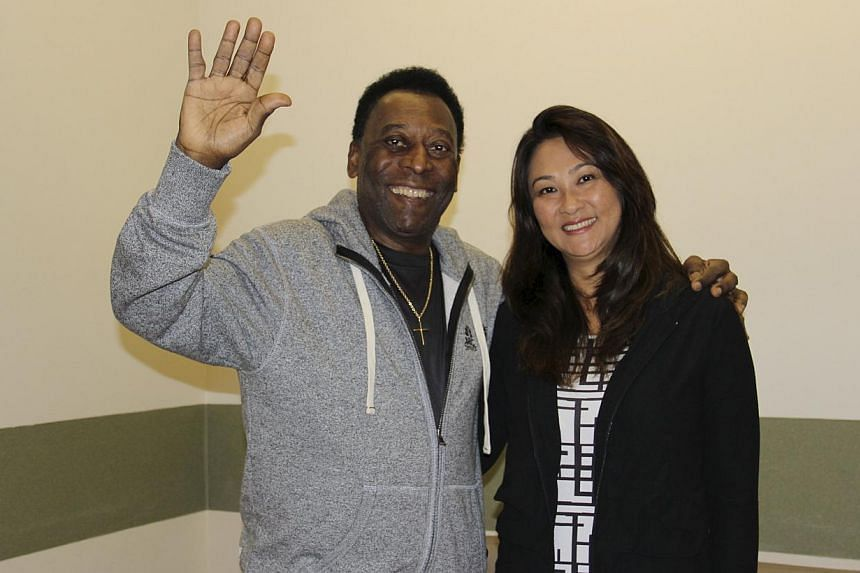 Brazilianfootball legend Pele (left) waves with his wife Marcia Cibele Aoki at the Albert Einstein Hospital in Sao Paulo in this May 9, 2015, handout photograph from his family, courtesy of the hospital. Brazilian football legend Pele was relea
