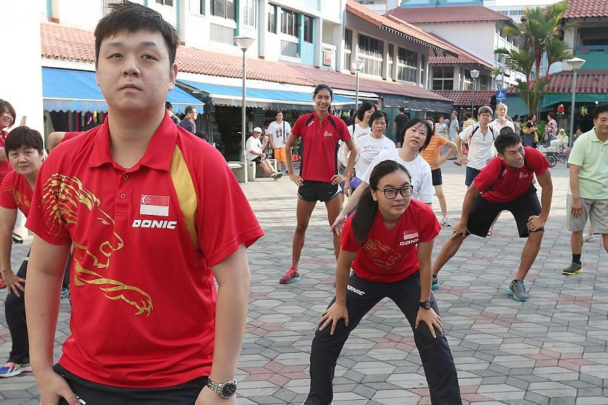 Team Singapore athletes like paddlers Li Hu (foreground), Isabelle Li (centre, hands on knees), hurdler Dipna Lim Prasad (background standing), and basketballer Wu Qing De (right, in red), join residents in a monthly community sporting event - Active
