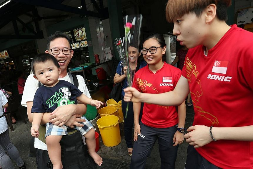 Team Singapore athletes, paddlers Zhou Yi Han (extreme right) and Isabelle Li (second from right) play with 13-month-old Loh Hau Wen, carried by his father Mr Sam Loh, 42. -- ST PHOTO: NEO XIAOBIN