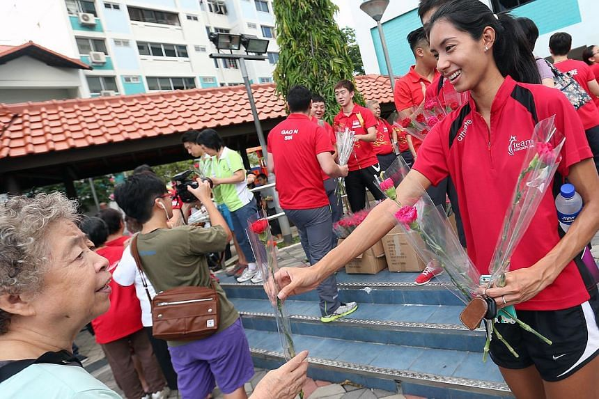 Team Singapore athlete, hurdler Dipna Lim Prasad (foreground right), joins residents in a monthly community sporting event - Active Day - at Khatib Plaza on May 10, 2015. -- ST PHOTO: NEO XIAOBIN