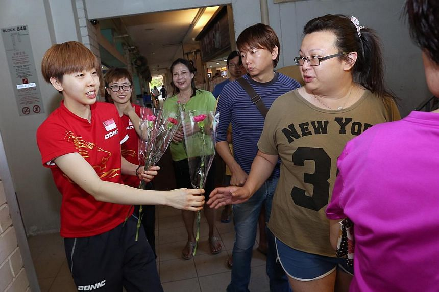 Team Singapore athletes, paddlers Zhou Yi Han (extreme left) and Feng Tian Wei (second from left) give out carnations for Mother's Day to the residents at a coffeeshop in Blk 848 Yishun Street 81. -- ST PHOTO: NEO XIAOBIN