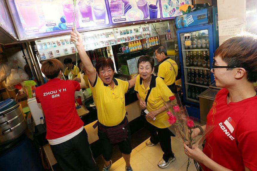 Coffeeshop runner Madam Ting Siew Kim (second from left), 73, reacts with her colleague Madam Lim Kwee Hoi (third from left), 74, after she receives a carnation from paddlers Zhou Yi Han (extreme left, back facing camera) and Feng Tian Wei (extreme r