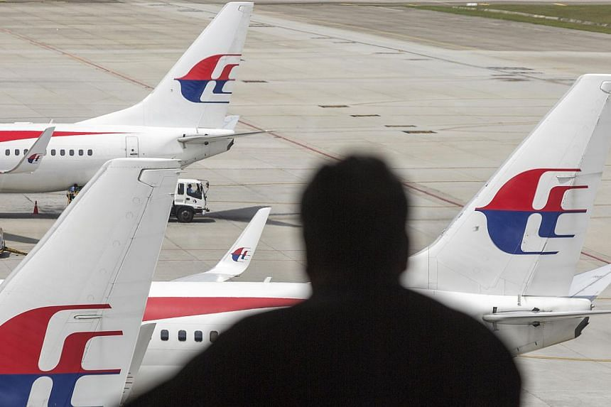 A silhouetted man looks out at aircraft operated by Malaysian Airline standing on the tarmac at Kuala Lumpur International Airport (KLIA) in Sepang, Malaysia, on Aug 26, 2014. -- PHOTO: BLOOMBERG