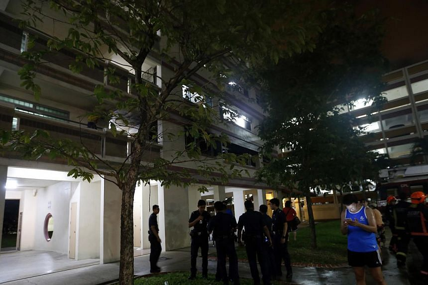 Police and Civil Defence officers and residents stand in the open after a unit in a block of flats along Tampines Street 33 caught fire on Sunday night. -- ST PHOTO: CHEW SENG KIM