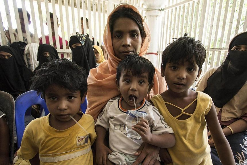 Migrant women and children from Myanmar and Bangladesh wait at a shelter in Matang Raya village, Baktya, in northern Aceh on May 10, 2015. Rescuers saved 469 boat people from Myanmar and Bangladesh who were stranded off the waters of Aceh on Sunday,