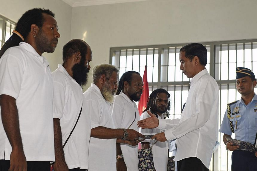 Indonesia's President Joko Widodo (right) handing over the official pardon to five political prisoners he granted clemency to, during a ceremony at a prison in Jayapura, Papua province, on May 9, 2015. President Widodo said on Sunday, May 10, that&nb