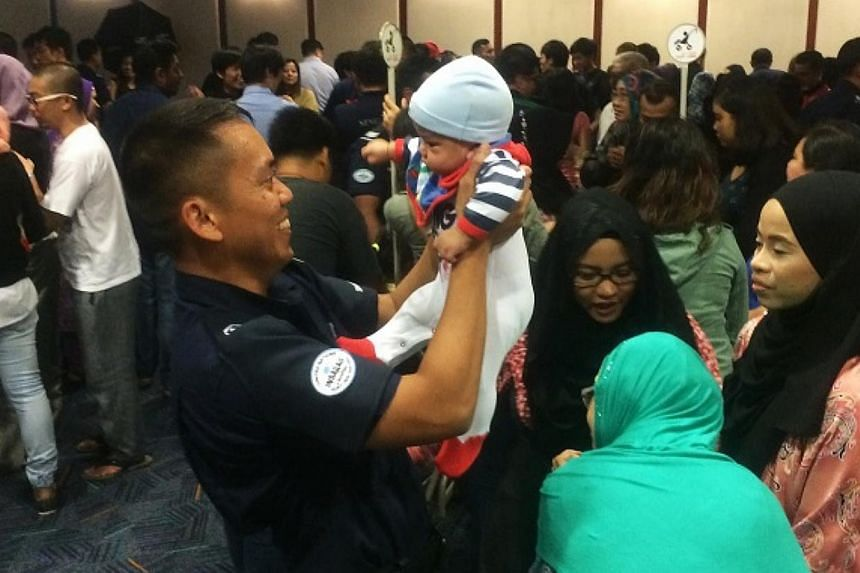 SCDF warrant officer Norherman Latib, 33, carries his four-month-old son Akhtar Umar Norherman, upon returning from the humanitarian mission in Nepal. Some 126 Home Team officers returned home on Saturday evening to a rousing welcome after spending t