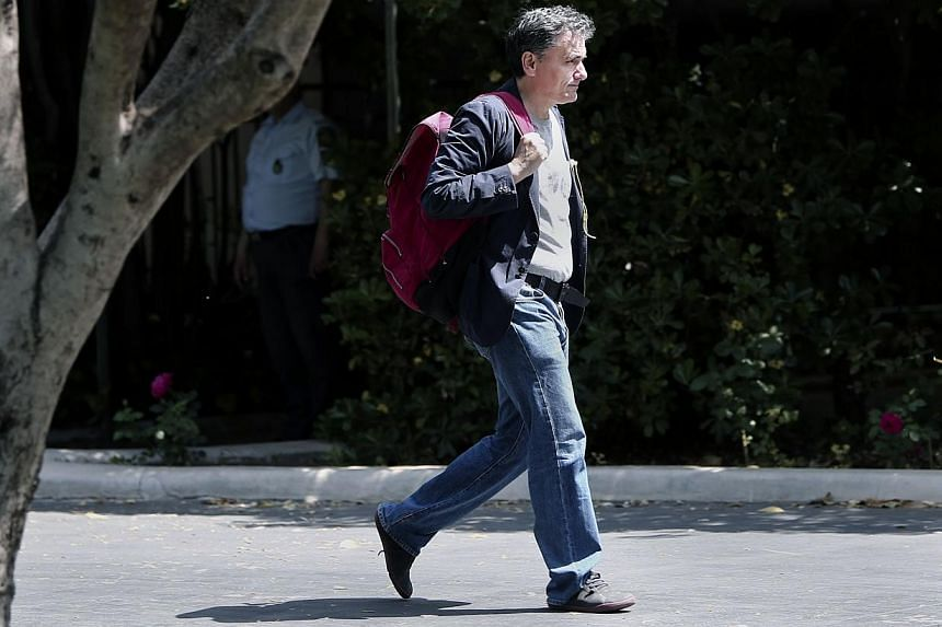 Wearing blue jeans, Greek minister of International Economic Relations Euclid Tsakalotos arrives for a cabinet meeting at the Prime minister's office in Athens on Sunday a day ahead a Eurogroup meeting. -- PHOTO: AFP