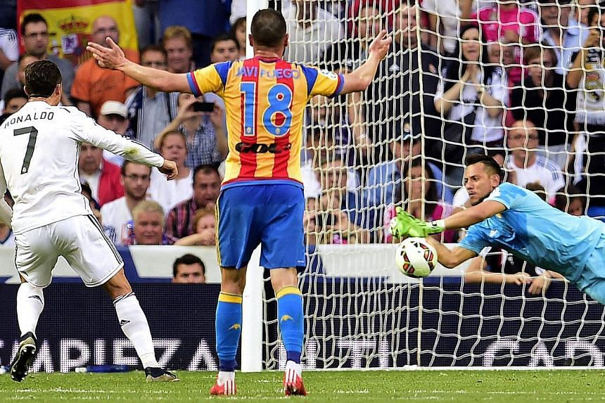 Valencia's goalkeeper Diego Alves (right) stops a penalty kick shot by Real Madrid's Portuguese forward Cristiano Ronaldo (left)on May 9, 2015. -- PHOTO: AFP