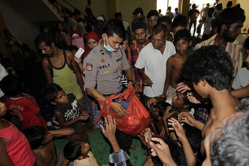 Rohingya refugees line up for breakfast in the sport stadium of Lhok Sukon, North Aceh, Sumatra, Indonesia on May 11,2015. Bangladeshi police arrested three human traffickers on Monday after killing four in recent days and arresting more than 1