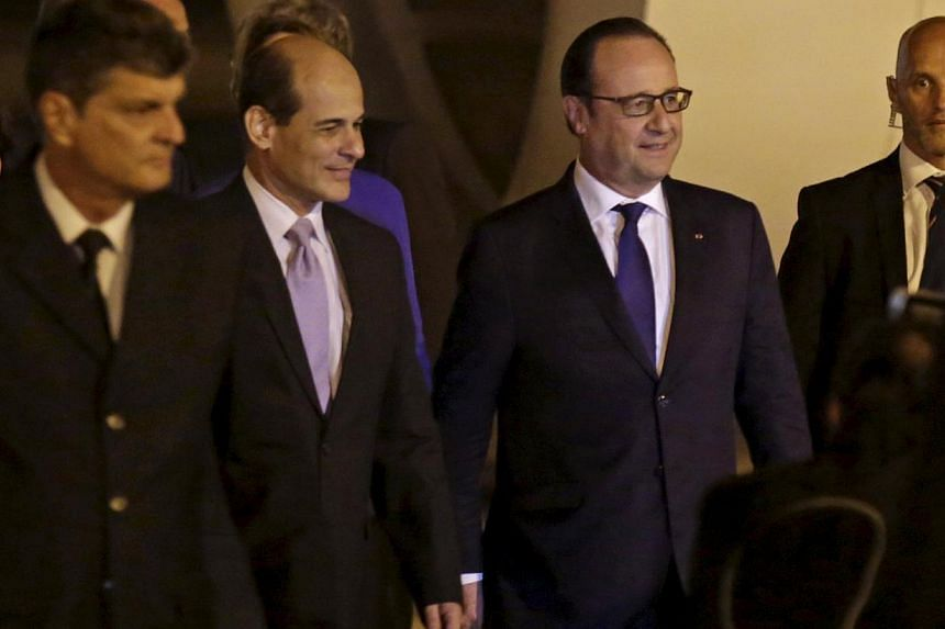 French President Francois Hollande (second from right) walks next to Cuba's Deputy Foreign Minister Rogelio Sierra (second from left) at Havana's Jose Marti airport on May 10, 2015. Mr Hollande is the first French president to visit Cuba in more than