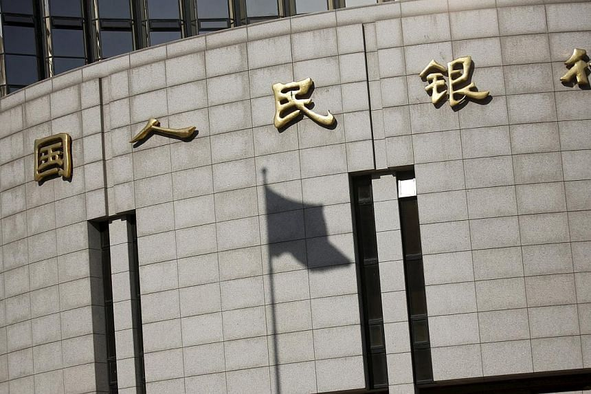 A fluttering Chinese national flag casts its shadow on the headquarters of the People's Bank of China, China's central bank, in central Beijing in this Nov 24, 2014 file photograph. China's central bank cut its benchmark interest rate on May 10, 2015