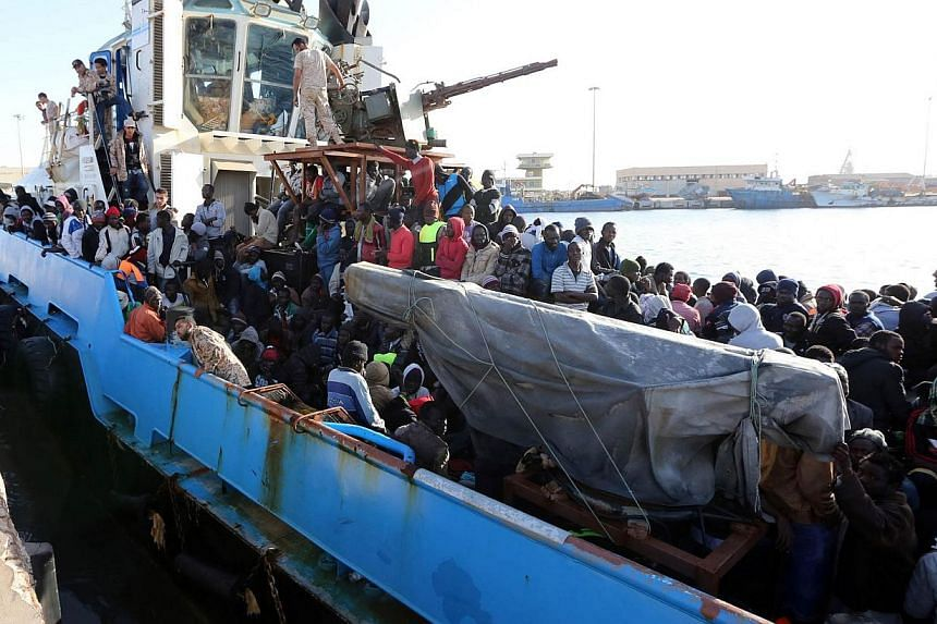 A Libyan coastguard boat carrying mostly African migrants arrive at the port in the city of Misrata on May 3, 2015, after the coastguard intercepted five boats carrying around 500 people trying to reach Europe. -- PHOTO: AFP