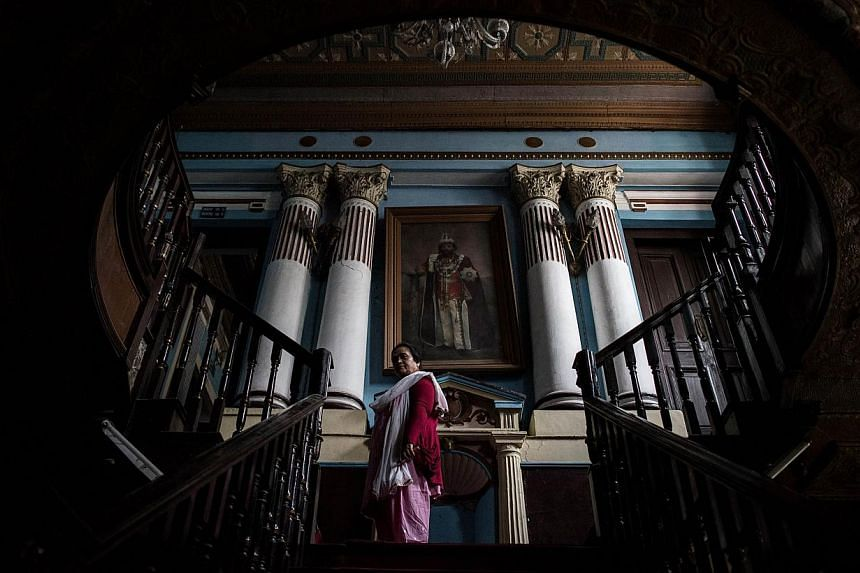 In this photo taken on May 7, 2015, chief librarian Janaki Karmacharya, 58, goes up the stairs of the Kaiser Library in Kathmandu. -- PHOTO: AFP