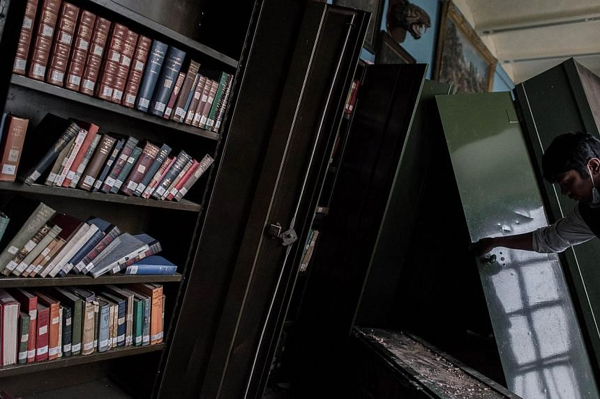 An employee looks at damaged book shelves at the Kaiser Library. -- PHOTO: AFP