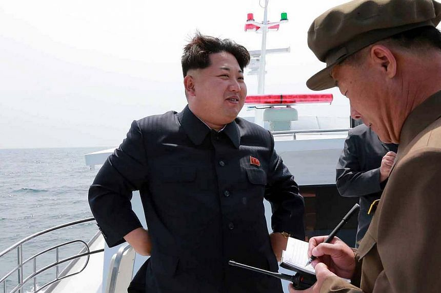 This undated picture released from North Korea's official Korean Central News Agency (KCNA) on May 9, 2015, shows the country's leader Kim Jong-Un smiling while observing an underwater test-fire of a submarine-launched ballistic missile at an undiscl