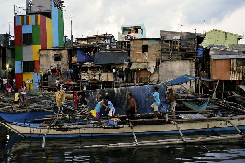 Filipino children walk above an anchored fishing boat in anticipation of typhoon Noul in Navotas city, north of Manila, on May 10, 2015. -- PHOTO: EPA