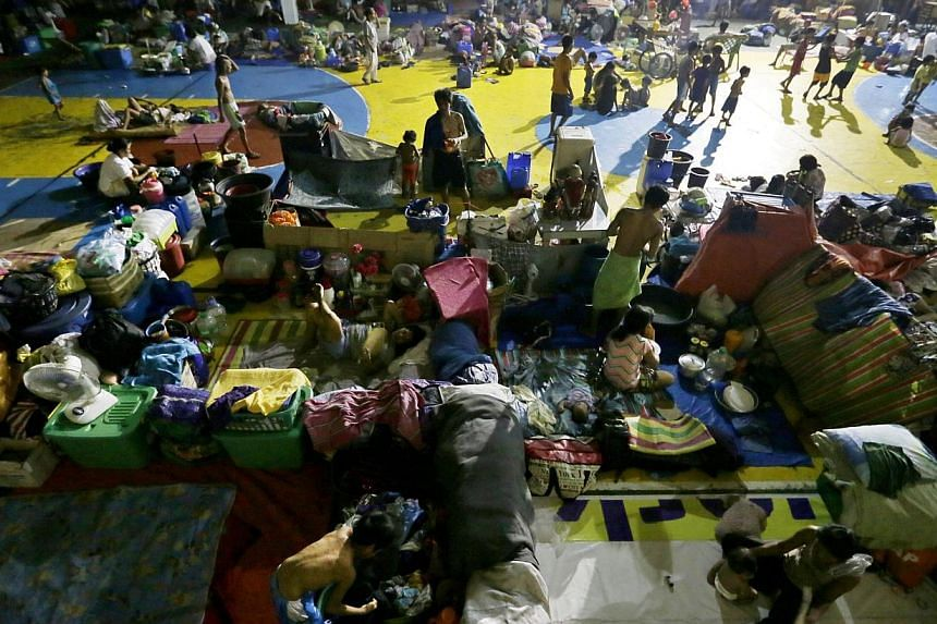 Filipino evacuees rest on a basketball court turned into temporary evacuation center in Manila on May 10, 2015. -- PHOTO: EPA