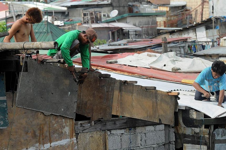 Residents along Manila Bay repair the roofs of their homes on May 10, 2015, in anticipation of Typhoon Noul as it approaches the northern Philippines. -- PHOTO: AFP